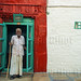 India, Rajasthan, Jodhpur. An old man with a stick stands on the porch of his house in the old town