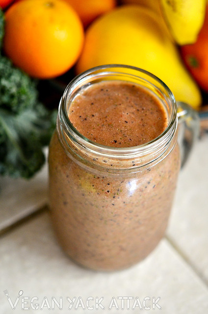 Speckled strawberry smoothie in a jar, in front of fruit and kale