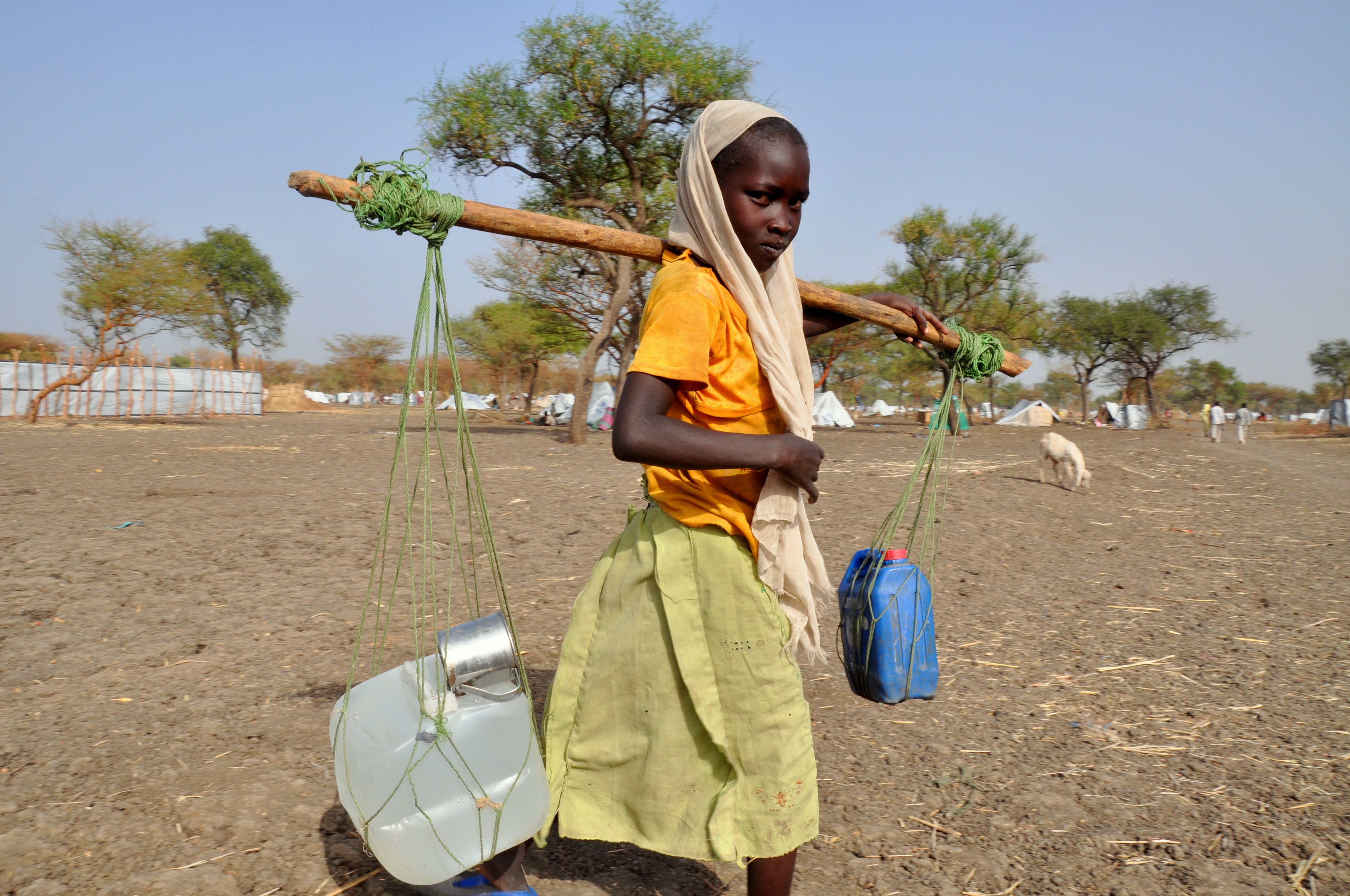 A young girl carries water back home, Jamam camp, South Sudan