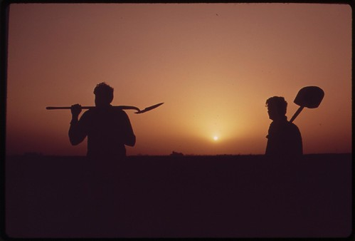 Farm workers shoulder tools at end of day near Ripley, in the fertile Palo Verde Valley of the lower Colorado River region, May 1972