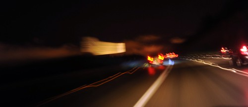 On the road, tail lights, vehicles on Highway 5, curve at night coming into Seattle, Washington, USA by Wonderlane