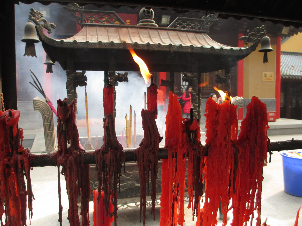 Red prayers | Beautiful candles and incense smoke at a templ