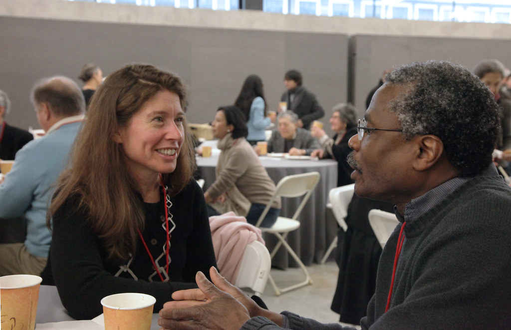 Department of Art faculty member Greg Page talking with an alumna at the faculty breakfast.