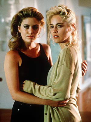 "This is a still from ""Basic Instinct."" Two women stand together, holding each other around the waist. They face the camera but their bodies are turned inward. One of the women has dirty blonde hair and is dressed in black. Her face is shadowed. The other woman has blonde hair and is dressed in beige."