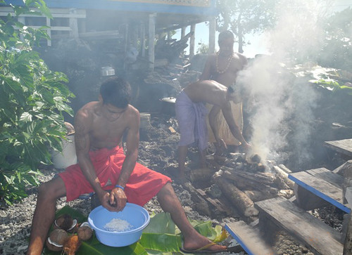 Preparing the umu, the boy in the foreground is scraping coconuts to make coconut cream while the men at the back are making a fire and filling it with stones that will heat up and cook the food.