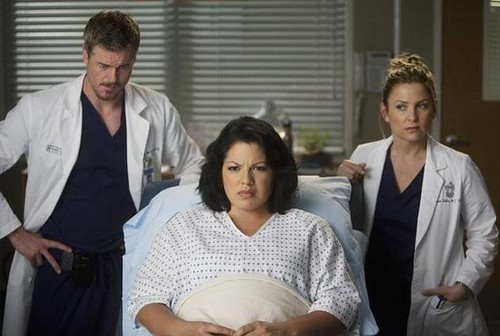 A woman in a hospital gown sits on an examining table in between a man and a woman dressed in doctor's scrubs. They have concerned looks on their faces.