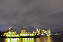 Tug boats and plane trail behind the plant