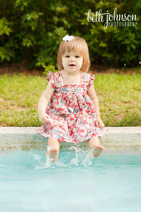 baby girl splashing her feet in reflecting pond blue water tallahassee