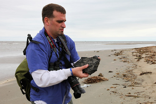 GRN's Jonathan Henderson examines a tar mat on Feb 24, 2012