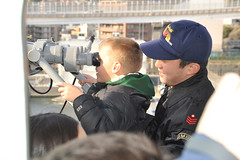 "YOKOSUKA, Japan (March 16, 2012) A Japan Maritime Self-Defense Force sailor assists the son of a U.S. Navy Sailor look through the ""Big Eyes"" aboard the Japan Maritime Self-Defense Force helicopter destroyer Hyuga (DDH 181) during the ship's Family Day Cruise. (U.S. Navy photo by Chief Mass Communication Specialist John Harrington)"
