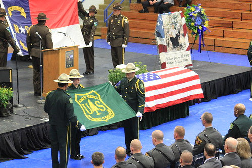 Honor Guard members begin to fold the U.S. Forest Service and North Carolina State flags during a memorial ceremony for Officer Jason Crisp and his K-9 partner Maros. (Courtesy of Mario Rossilli)
