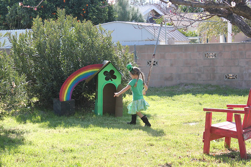 child playing near leprechaun cardboard house