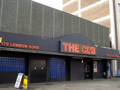 "The right-hand side of the block again, with the same dark blue tiling, double entrance doors, and black-painted surround as earlier, but the Cartoon sign has been replaced by one simply reading ""The Club"" in red on black, with the address and phone number on either side."