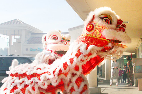 Lion Dancers Performing in Front of a Store