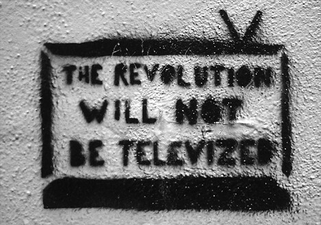"A black and white grafitti image of a rabbit eared tv set bearing the words ""the revolution will not be televized"" (sic)"