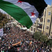 Syria independence flag flies over a large pathering of protesters in Idlib.