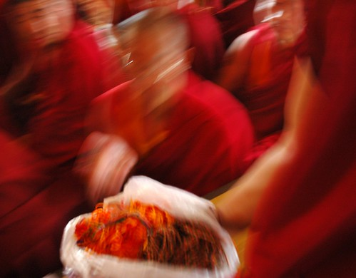 Senior Tibetan Lama blowing a blessing onto blessing cords held by a monk, red robes, Sakya Lamdre, Tharlam Monastery of Tibetan Buddhism, Boudha, Kathmandu, Nepal by Wonderlane