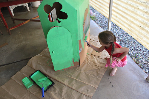 child painting cardboard house with green paint