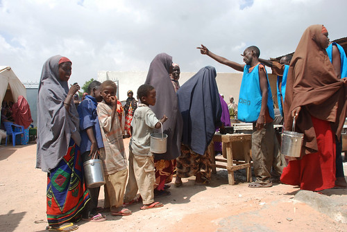 Children and mothers await food at distribution site