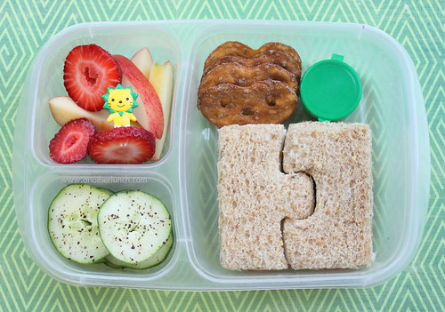 Puzzle sandwich, organic apples & strawberries, cukes, pretzels & tiny treat