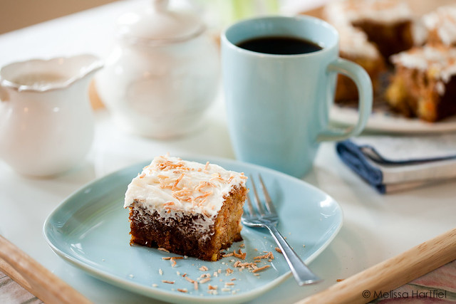 A slice of carrot cake and a cup of tea by a bright window