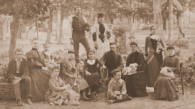 "Group probably taken at ""The Cottage"", Lakeside. Standing: William Clark & Ida Oram. Front from left: Arthur Oram, Anna Clark, wife of William with their son Arvin born 1884, two unknown girls, Lillian Louise Oram, John ""BaBa"" Oram, Oscar Oram cross-legged, Jane Oram with dog, Emma Jean Oram & Jessie Simon."