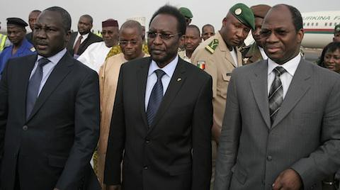 Dioncounda Traore, center, Mali's parliamentary head who was forced into exile after last month's coup, walks with Burkina Faso's Foreign Affairs Minister Djibrill Bassole, right, as Traore arrives in Bamako to take up his constitutionally-mandated post. by Pan-African News Wire File Photos