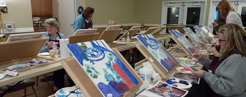 Group of women painting on table top easels after wine and appetizers