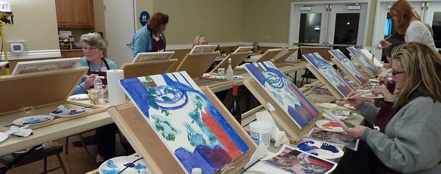 Photo of women sitting at individual table easels painting with acrylic paints.