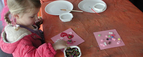 Little girl creating an art piece using glitter and hearts.