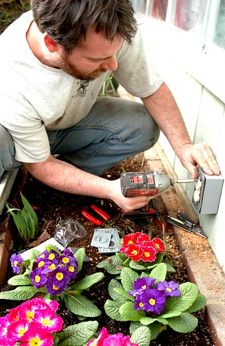 Electrician Stephen installing an exterior electric plug using a portable electric screwdriver, spring flowers, Seattle, Washington, USA by Wonderlane