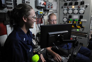 Lt. j.g. Claire L. Miller talks with duty watchstanders in the engine room aboard the Coast Guard Cutter Dauntless Feb. 20, 2014. As the damage control assistant, Miller is responsible for maintaining the ship's watertight integrity and ensuring the ship can respond effectively to any damage that may be incurred. (U.S. Coast Guard photo by Petty Officer 3rd Class Mark Barney)