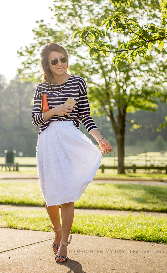navy striped top with pom poms, orange clutch, white midi skirt, jeweled sandals