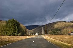 Soleil et ciel noir sur la route