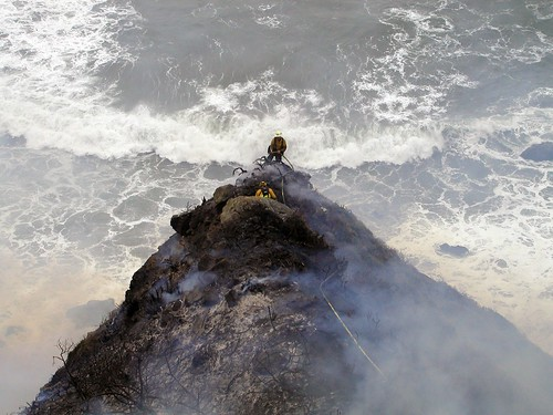 "Los Padres firefighter Kevin Poyner (facing camera) and John Knight of the Big Sur Volunteer Fire Brigade appear to have one foot ""in the black"" and the other in the Pacific Ocean. In reality, the two men have ample room between their position and the cliffs leading down to the beach."