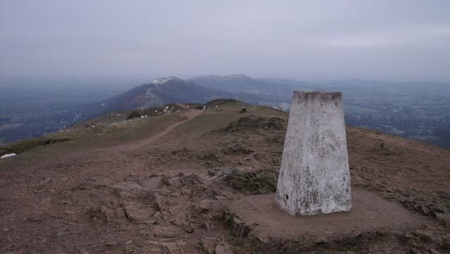 Trig point at the peak of Worcestershire Beacon, with the southern Malvern Hills beyond and below