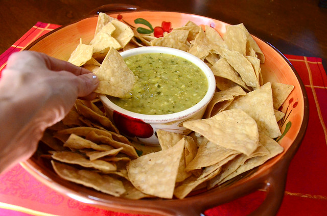 A chip being dipped into Roasted Tomatillo Salsa.