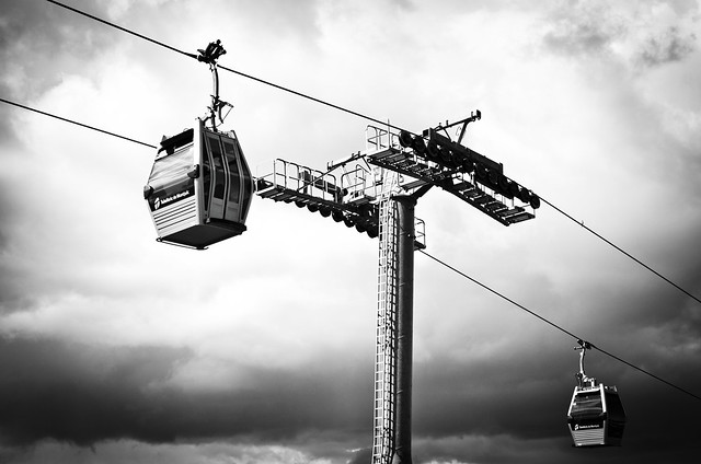 Cable cars slide through a cloudy sky from the hilltop Montjuïc down to Barceloneta beach.