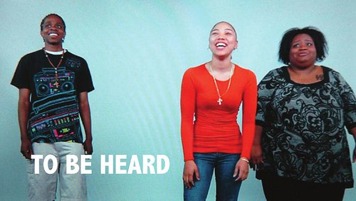 Image for the film to be heard. Three women laughing and the words appear in white between them