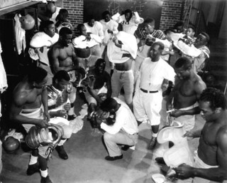 Coach Jake Gaither (standing, middle, white shirt) in the locker room with his Florida Agricultural and Mechanical University (FAMU) football team: Tallahassee, Florida