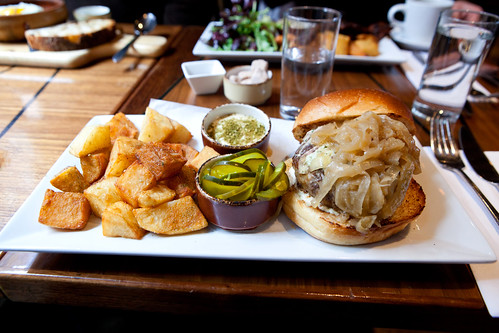 Lamb burger Stuffed with Herbed Goat Cheese, served with Caramelized Onions, Brioche Bun, Patatas Bravas