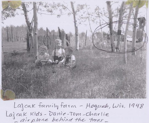 Out at the farm with a plane in the background, 1948.