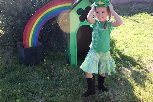 smiling child standing in front of a cardboard leprechaun house
