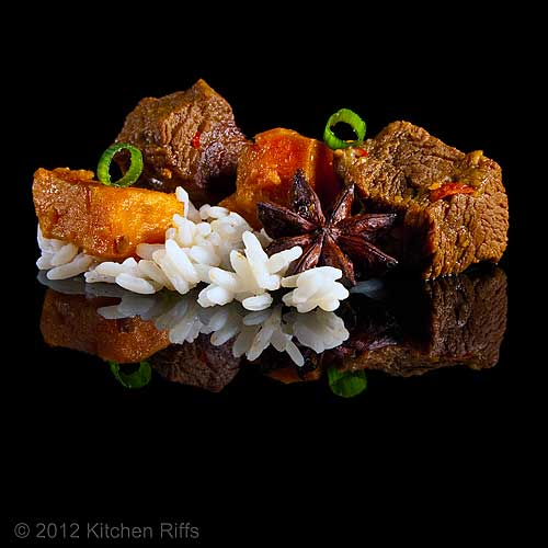 Red-Braised Beef with Sweet Potatoes and Rice on Black Acrylic