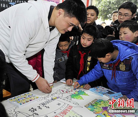 February 17, 2012 - Yao Ming and wife Ye Li visit with children at a school that will be refurbished by Yao Ming's Foundation