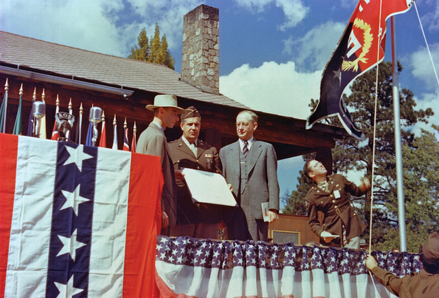 "Gen. Leslie Groves (center), head of the Manhattan Project, presented the Army-Navy ""E"" Award flag to the Laboratory on October 16, 1945, with Lab Director J. Robert Oppenheimer (left) and University of California President Robert Sproul (right) looking on. The War Department citation reads: ""in Recognition of Research and Development of the Atomic Bomb to the Men and Women of the University of California, Los Alamos Scientific Laboratory.""   Only 5 percent of eligible  production plants won the Army-Navy ""E"" Award during World War II.   Article from National Security Science available at: <a href=""http://www.lanl.gov/science/NSS/issue1_2012/story9.shtml"" rel=""noreferrer nofollow"">www.lanl.gov/science/NSS/issue1_2012/story9.shtml</a>"