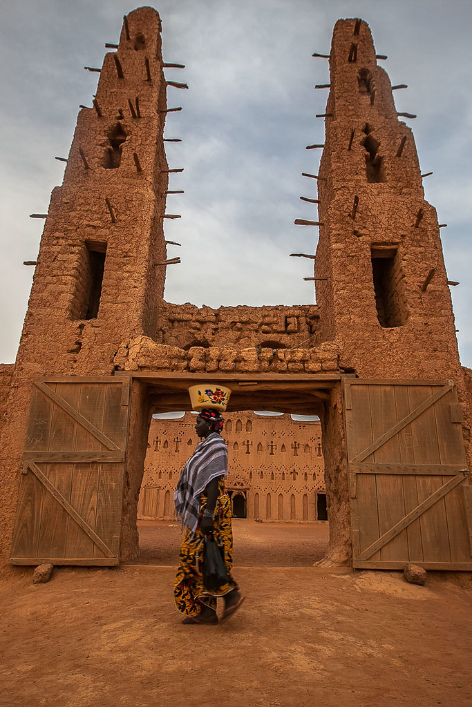 woman with a pot on his head at the main entrance of the great mud mosque of bani, in the tribal region of the Sahel, northern Burkina Faso