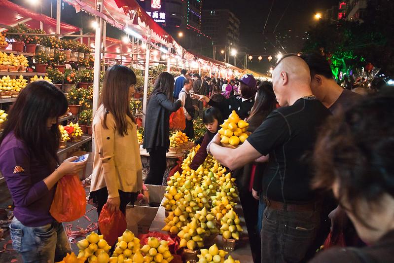 Chinos comprando limones en un puesto callejero de un mercadillo de Guangzhou.