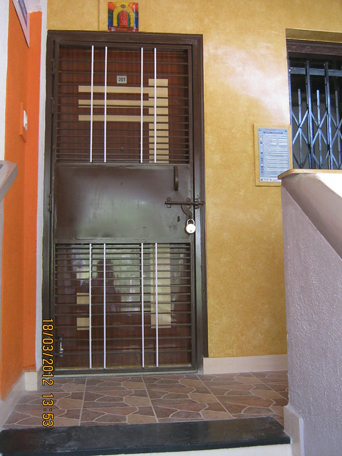 Decorative main door with m s safety door of a flat in san for Designs for main door of flat