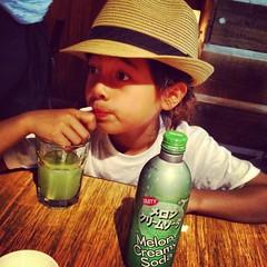 my daughter in my hat drinking strange green soda